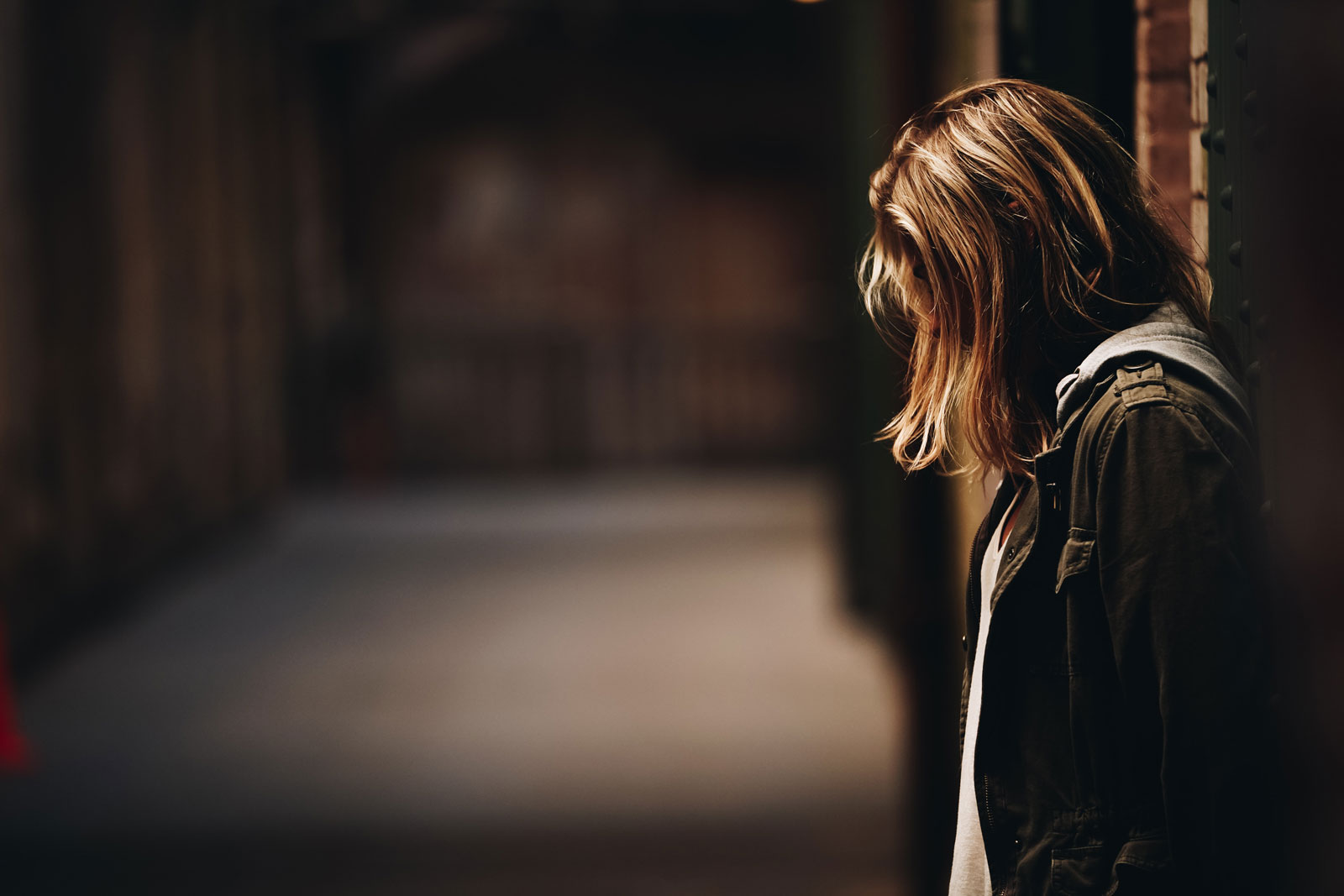 woman standing in a dark alley with head down in saddness