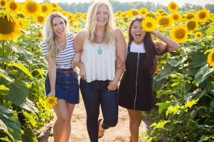 3 smiling women standing in a sunflower crop and smiling