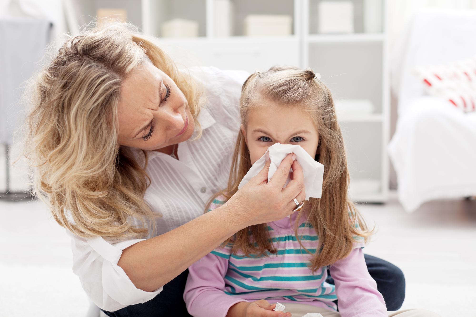 women helping child blow their nose